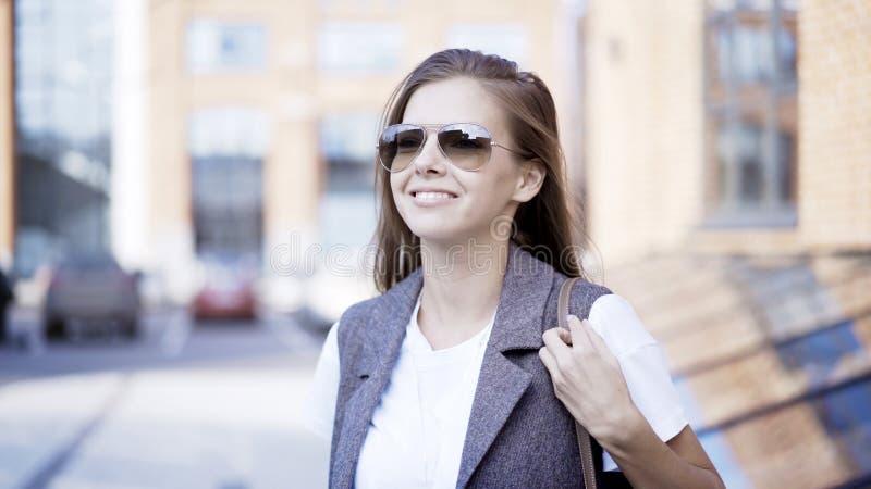 Ένα νέο χαμογελώντας κορίτσι φορά τα γυαλιά υπαίθρια στοκ εικόνες με δικαίωμα ελεύθερης χρήσης