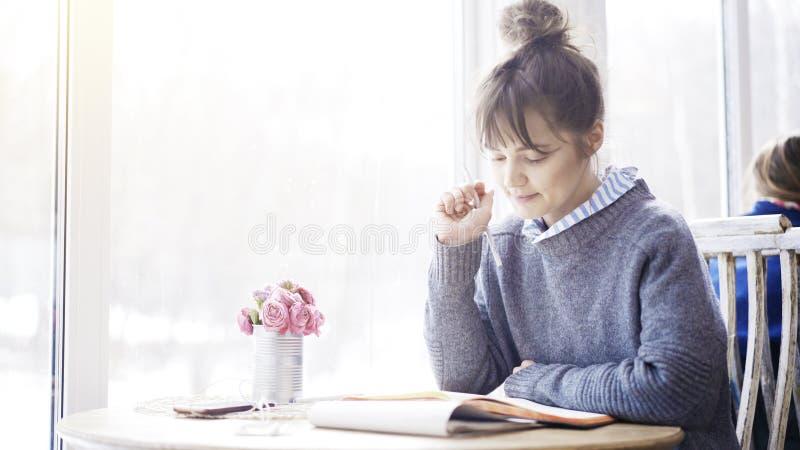 Ένα νέο χαμογελώντας κορίτσι brunette διαβάζει ένα σημειωματάριο στον καφέ στοκ φωτογραφίες με δικαίωμα ελεύθερης χρήσης