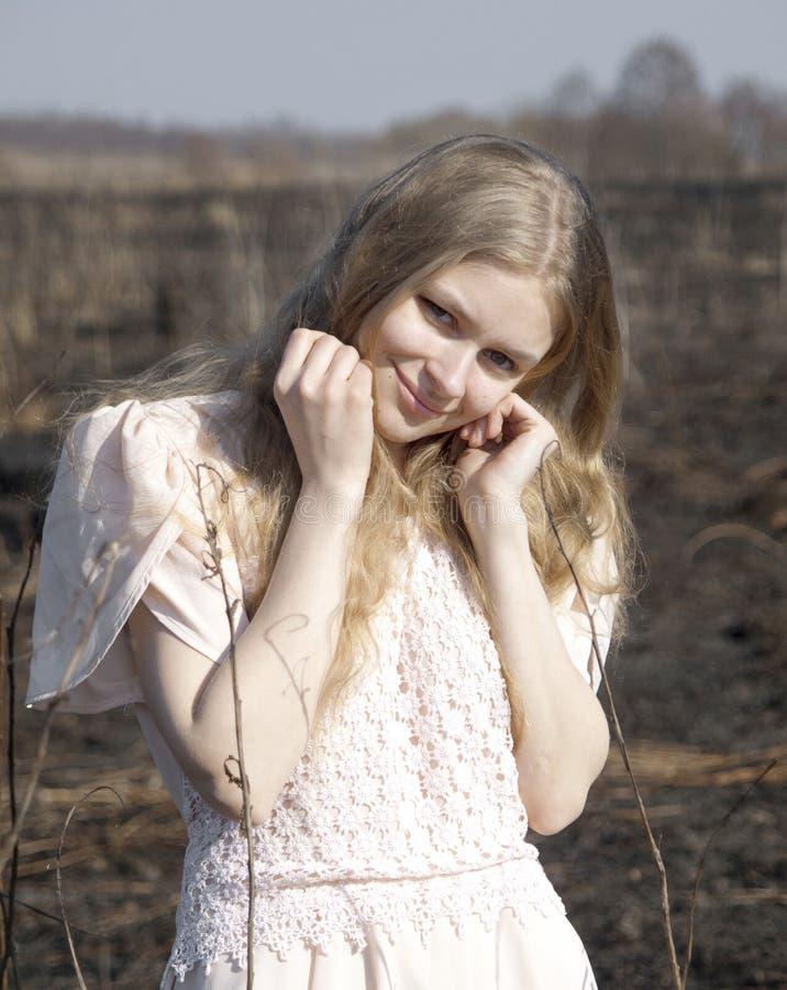 Ένα νέο όμορφο κορίτσι στο ελαφρύ κοντός-sleeved φόρεμα κλίνει το μάγουλό της στην πυγμή της στοκ εικόνες
