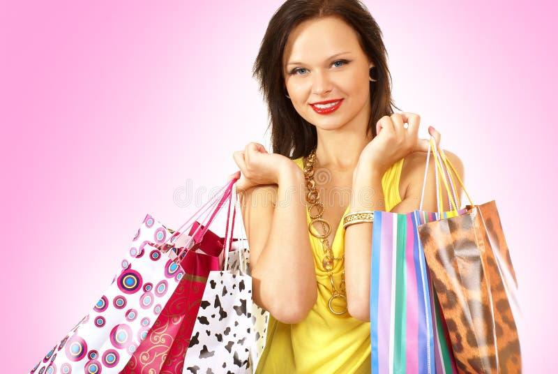 Ένα νέο brunette με τις τσάντες αγορών στοκ εικόνες