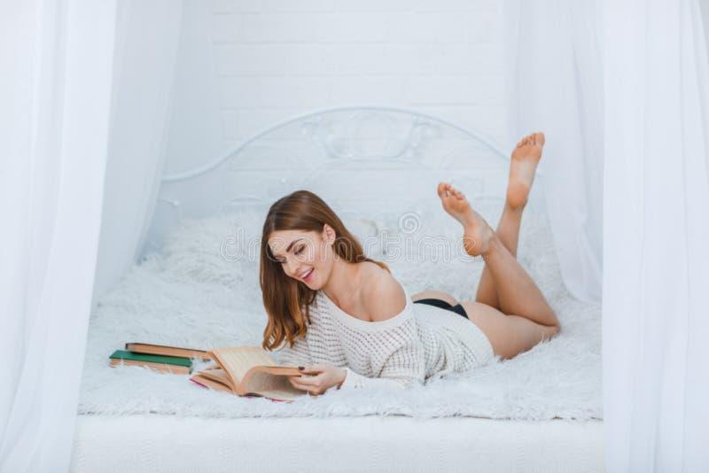 Ένα να βρεθεί νέων κοριτσιών κρεβάτι στην κρεβατοκάμαρα και χαρωπά να διαβάσει τα βιβλία στοκ φωτογραφία με δικαίωμα ελεύθερης χρήσης