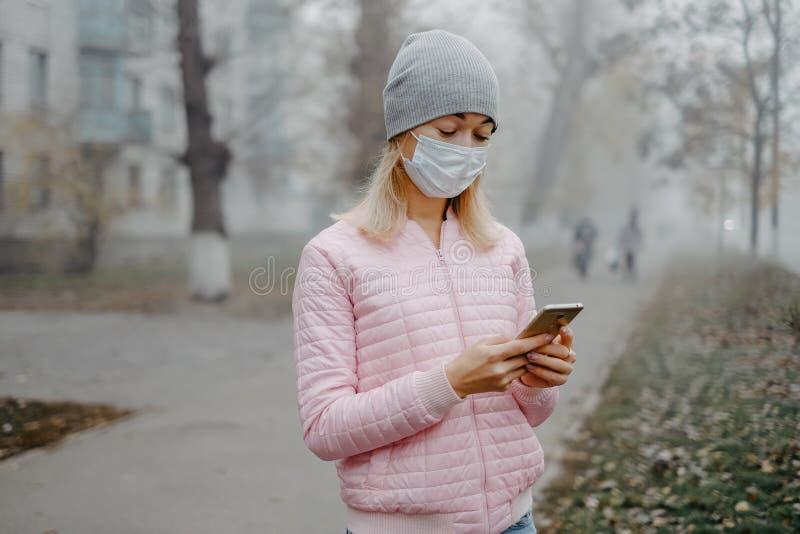 Ένα νεαρό κορίτσι στέκεται κοντά στο δρόμο με ιατρική μάσκα Προστασία από επιδημία ιών σε πόλη στοκ φωτογραφία με δικαίωμα ελεύθερης χρήσης