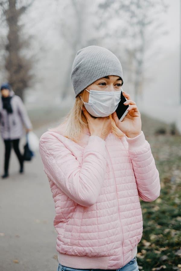 Ένα νεαρό κορίτσι στέκεται κοντά στο δρόμο με ιατρική μάσκα Προστασία από επιδημία ιών σε πόλη στοκ φωτογραφίες με δικαίωμα ελεύθερης χρήσης