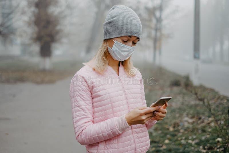 Ένα νεαρό κορίτσι στέκεται κοντά στο δρόμο με ιατρική μάσκα Προστασία από επιδημία ιών σε πόλη στοκ εικόνες