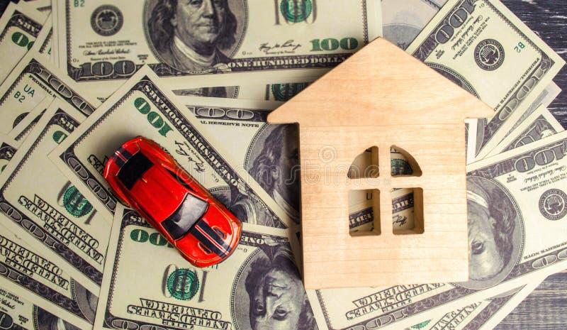Ένα ξύλινα πρότυπο και ένα αυτοκίνητο σπιτιών με τα αμερικανικά δολάρια αγορά και πώληση ή ασφάλεια αυτοκινήτου Έννοια της επιχει στοκ εικόνες