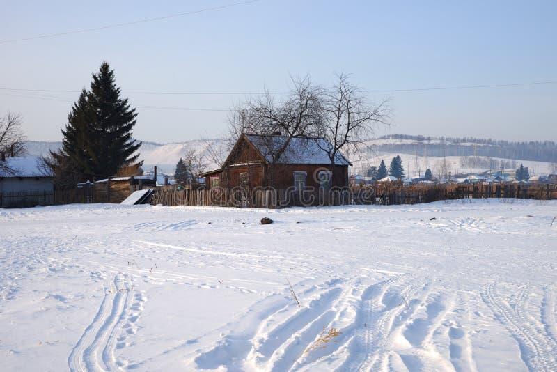 Ένα ξύλινο μικρό σπίτι στέκεται σε έναν χιονώδη λόφο στο χωριό στοκ εικόνα