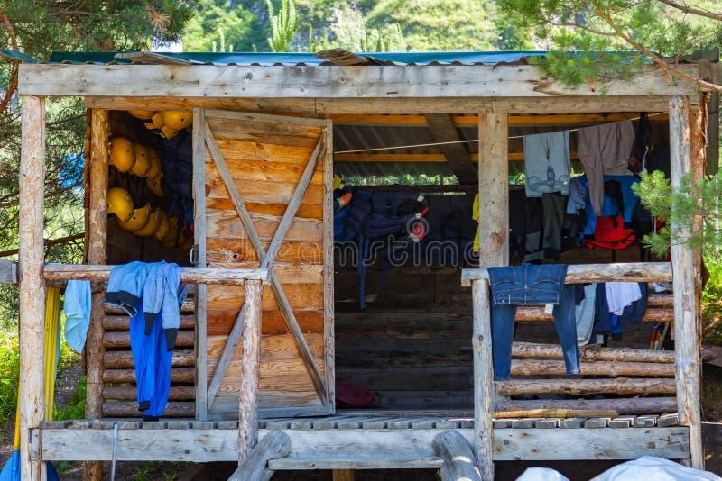 Ένα ξύλινο σπίτι, μια καλύβα στο δάσος κοντά σε έναν ποταμό βουνών με τα ενδύματα, τα κράνη και το rafting εξοπλισμό, τις μπλούζε στοκ φωτογραφία με δικαίωμα ελεύθερης χρήσης