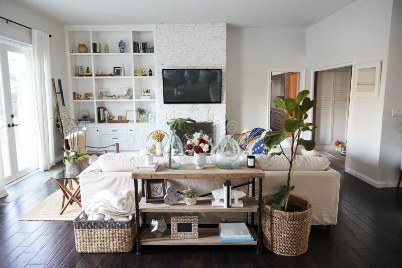 Ένα οικογενειακό καθιστικό με τους άσπρους τοίχους και σκοτεινά ξύλινα floorboards που βλέπουν στο φως της ημέρας, από πίσω από τ στοκ φωτογραφίες με δικαίωμα ελεύθερης χρήσης