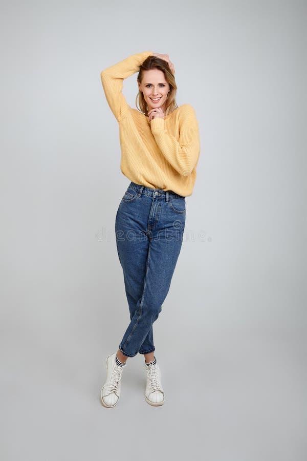 Ένα ολόκληρο πορτρέτο όμορφου ενός ξανθού, που ντύνεται στα μοντέρνα ενδύματα Με ένα χέρι κρατά την τρίχα του και το άλλο χέρι κρ στοκ φωτογραφίες με δικαίωμα ελεύθερης χρήσης