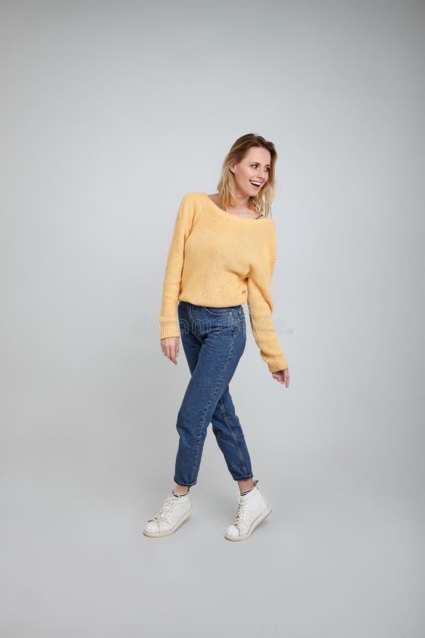 Ένα ολόκληρο πορτρέτο όμορφου ενός ξανθού, που ντύνεται στα μοντέρνα ενδύματα θέτει μπροστά από το άσπρο υπόβαθρο στοκ εικόνα με δικαίωμα ελεύθερης χρήσης