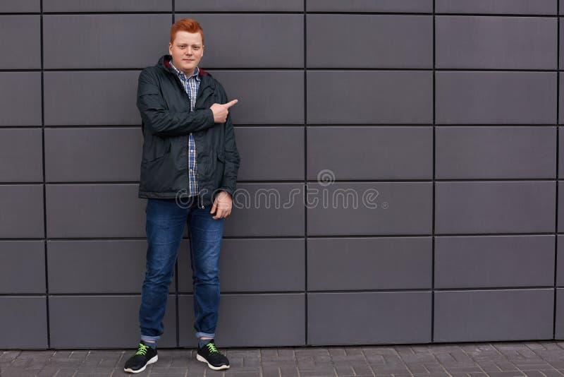 Ένα οριζόντιο πορτρέτο του μοντέρνου redhead ατόμου έντυσε στα ελεγχμένα τζιν σακακιών πουκάμισων μαύρα και τα τρέχοντας παπούτσι στοκ εικόνες