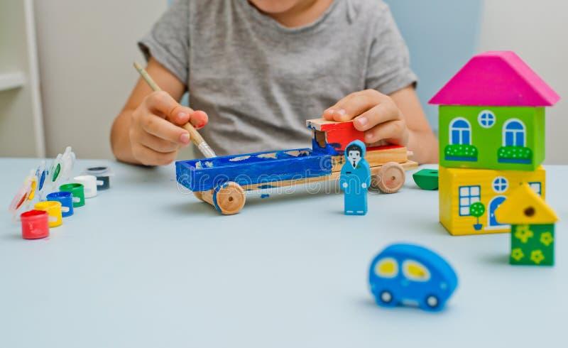 Ένα παιδί παίζει στο γραφείο του με το watercolor, σύροντας τα ξύλινα μέρη του ξύλινου παιχνιδιού του στοκ φωτογραφίες με δικαίωμα ελεύθερης χρήσης
