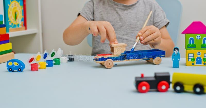 Ένα παιδί παίζει στο γραφείο του με το watercolor, σύροντας τα ξύλινα μέρη του ξύλινου παιχνιδιού του στοκ εικόνες