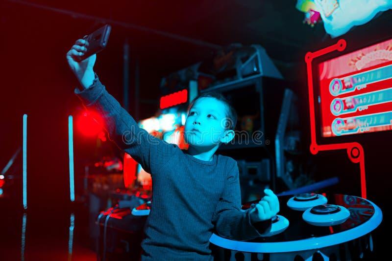 Ένα παιδί παίρνει ένα selfie Το αγόρι κρατά το τηλέφωνο στα χέρια του Φωτισμός νέου Κινητά παιχνίδια στοκ φωτογραφία με δικαίωμα ελεύθερης χρήσης