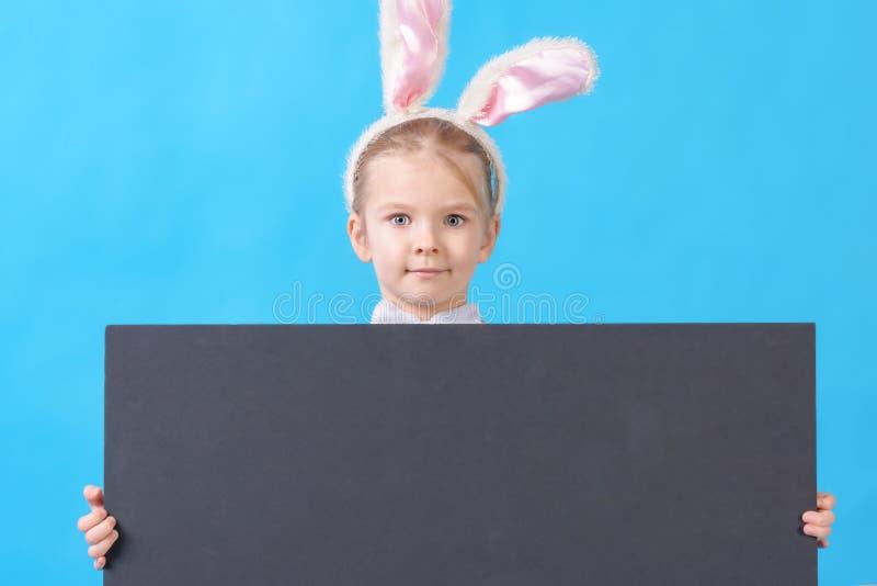 Ένα παιδί σε ένα άσπρο κοστούμι κουνελιών σε ένα μπλε υπόβαθρο Ένα χαριτωμένο μικρό κορίτσι με τα αυτιά ενός λαγού κρατά στα χέρι στοκ εικόνες με δικαίωμα ελεύθερης χρήσης
