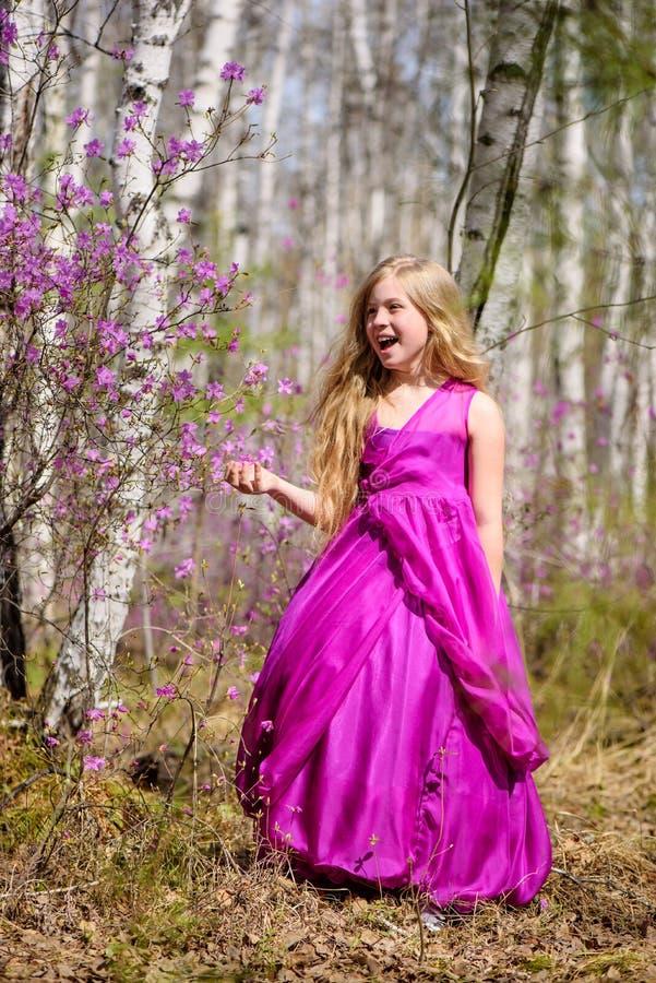 Ένα παιδί στέκεται μεταξύ του ledum και της σημύδας σε ένα ρόδινο φόρεμα και γελά στοκ φωτογραφία με δικαίωμα ελεύθερης χρήσης
