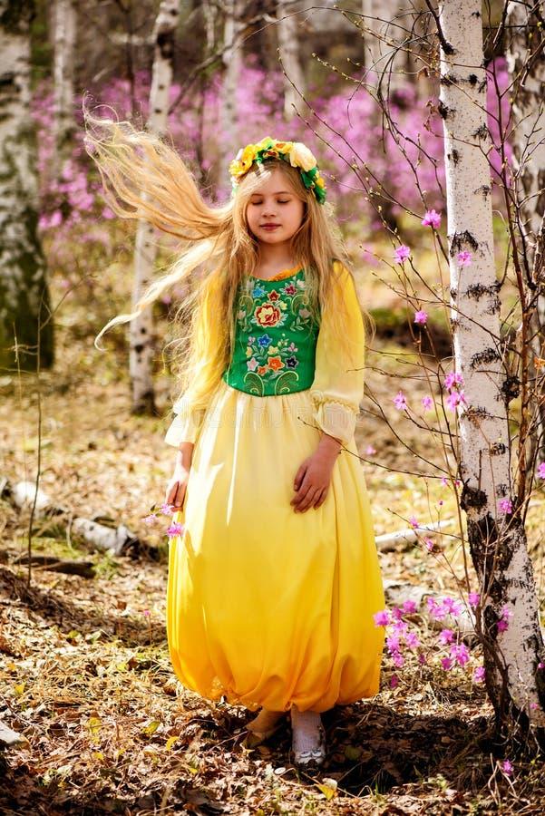 Ένα παιδί στέκεται μεταξύ του ledum και της σημύδας στο πράσινο κίτρινο φόρεμα, χαμογελώντας και πετά την τρίχα στοκ φωτογραφίες με δικαίωμα ελεύθερης χρήσης