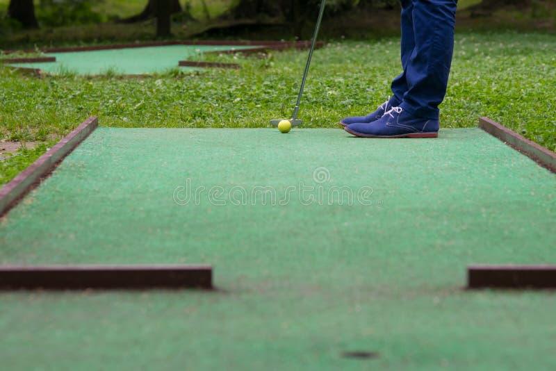 ένα παιχνίδι του μίνι-γκολφ, μια άποψη από την τρύπα κατά την διάρκεια του χτυπήματος μιας κίτρινης σφαίρας με ένα ραβδί στοκ φωτογραφία με δικαίωμα ελεύθερης χρήσης