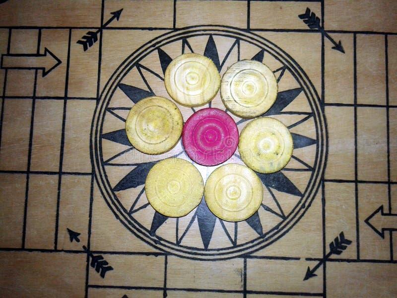 Ένα παιχνίδι του carrom με τα κομμάτια carrom επανδρώνει στον πίνακα carom - συσσωρεύοντας στοκ φωτογραφίες