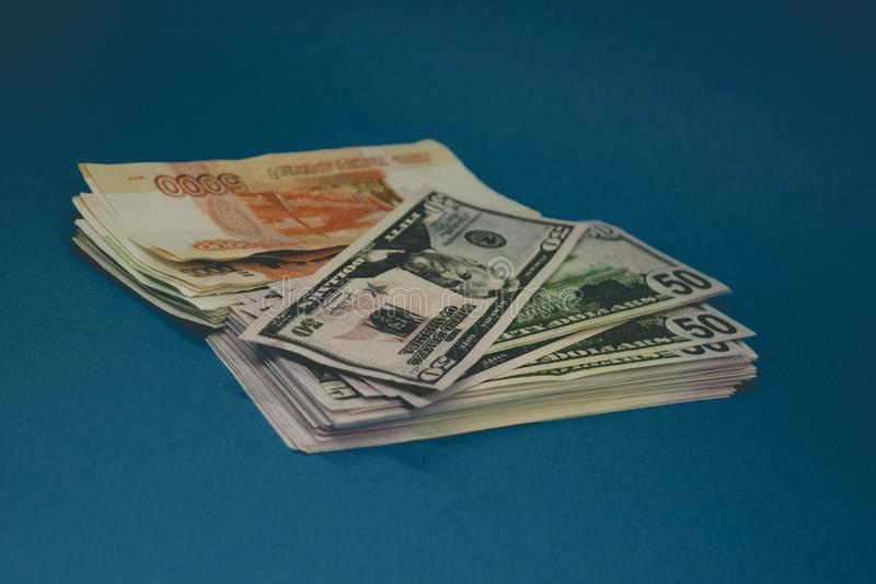 ένα πακέτο των ρωσικών ρουβλιών και των δολαρίων δύο wads των χρημάτων σε ένα μπλε υπόβαθρο πλούτος της ευκαιρίας επιτυχία στοκ εικόνες με δικαίωμα ελεύθερης χρήσης