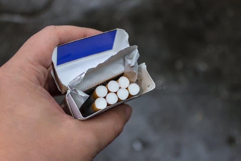 Ένα πακέτο των τσιγάρων στα χέρια του Ζημιά στην υγεία από το κάπνισμα στοκ φωτογραφίες