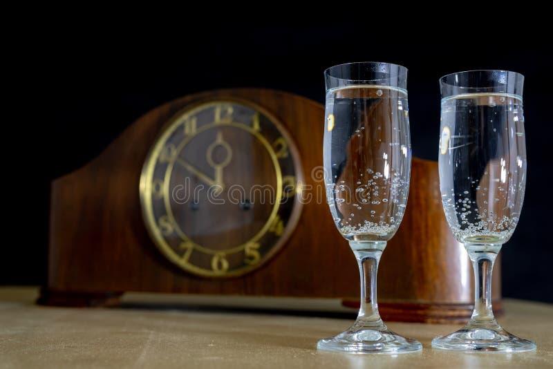 Ένα παλαιά ρολόι και ένα σύνολο γυαλιών της σαμπάνιας σε νέο Year' παραμονή του s Fi στοκ εικόνες