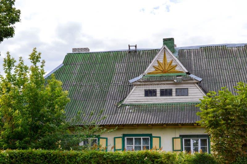 Ένα παλαιό αγροτικό ξύλινο ευρωπαϊκό εξοχικό σπίτι σπιτιών φιαγμένο από πίνακες με τα παράθυρα με τα παραθυρόφυλλα με μια τριγωνι στοκ φωτογραφίες με δικαίωμα ελεύθερης χρήσης