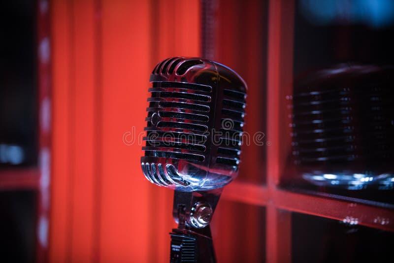 Ένα παλαιό αναδρομικό μικρόφωνο ύφους στο κόκκινο υπόβαθρο κλείστε επάνω στοκ εικόνες