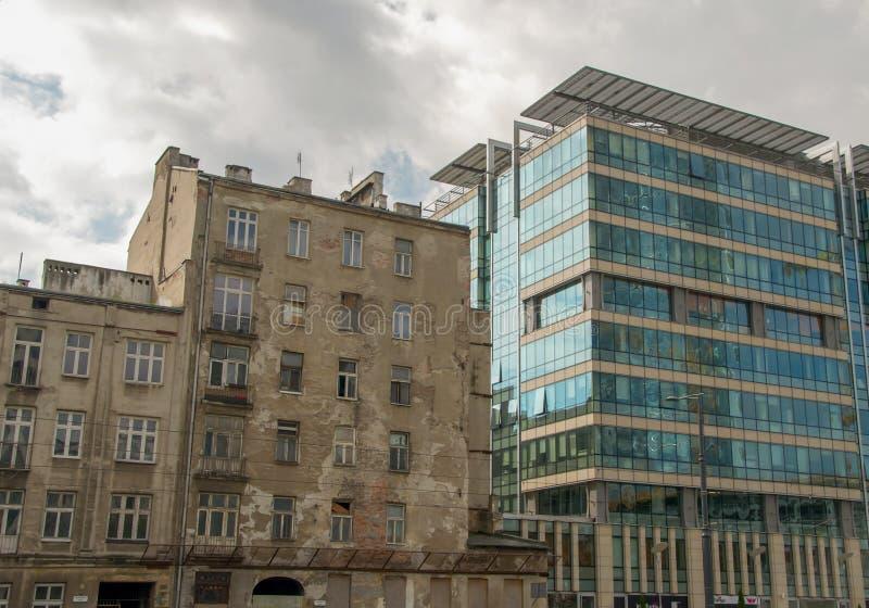 Ένα παλαιό εγκαταλειμμένο σπίτι κατοικιών και ένα σύγχρονο εμπορικό κέντρο Βαρσοβία, Πολωνία στοκ φωτογραφίες