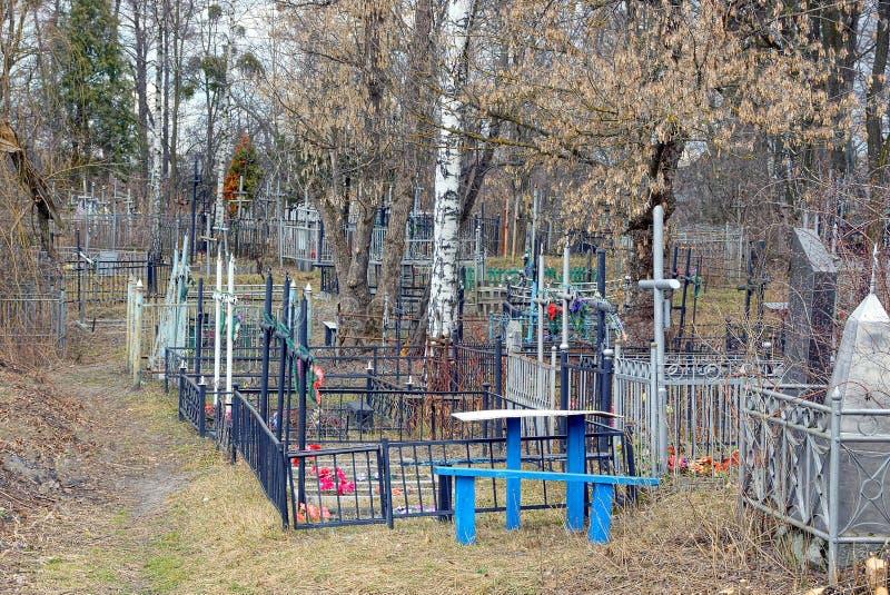 Ένα παλαιό νεκροταφείο με τους σταυρούς και τους φράκτες στην ξηρά χλόη και τα δέντρα στοκ φωτογραφία