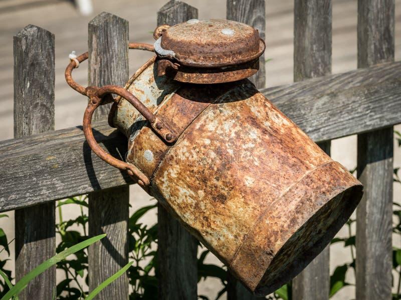 Ένα παλαιό σκουριασμένο καρδάρι γάλακτος που κρεμά σε έναν ξύλινο φράκτη στοκ εικόνα