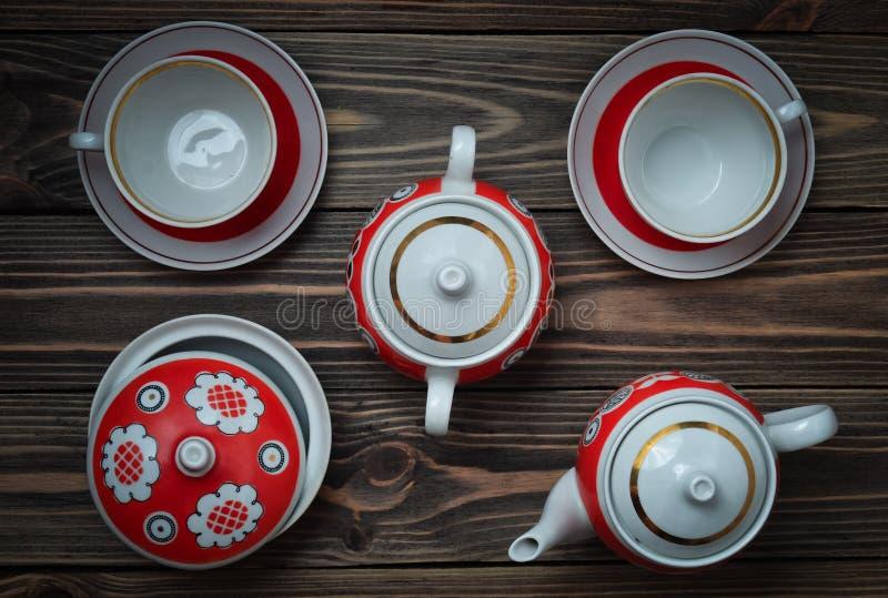 Ένα παλαιό σύνολο κεραμικά teapots, φλυτζάνια, πιατάκια σε έναν ξύλινο πίνακα Τελετή τσαγιού στοκ εικόνα με δικαίωμα ελεύθερης χρήσης