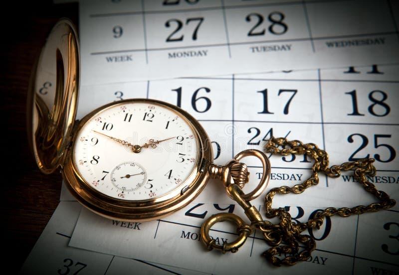 Ένα παλαιό χρυσό ρολόι τσεπών βρίσκεται στα ημερολογιακά φύλλα στοκ εικόνες με δικαίωμα ελεύθερης χρήσης