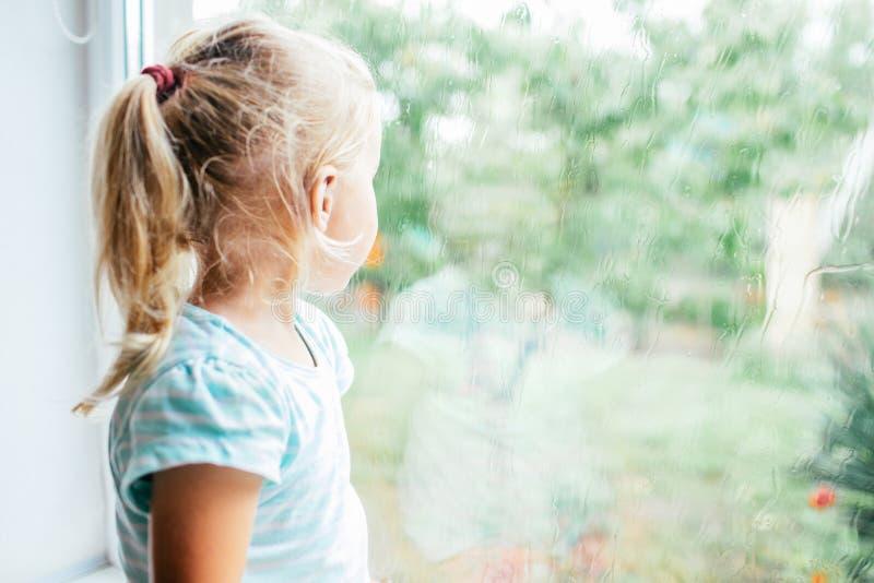 Ένα πανέμορφο ξανθό μικρό κορίτσι με το ponytale που κοιτάζει επίμονα από το παράθυρο μια υγρή, κρύα βροχερή θερινή ημέρα στοκ εικόνες