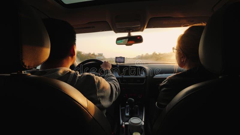 Ένα παντρεμένο ζευγάρι ταξιδεύει με το αυτοκίνητο, ο ήλιος ρύθμισης τους φωτίζει Ασιατική οδήγηση ατόμων στοκ εικόνα