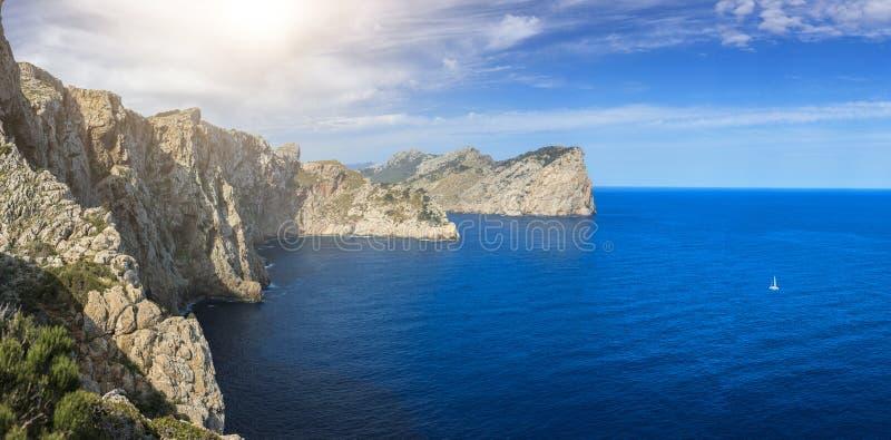 Ένα πανόραμα των απότομων βράχων στην ακτή Pollença, της Μαγιόρκα και ενιαίο άσπρο sailboat στα όμορφα μπλε νερά στοκ φωτογραφίες με δικαίωμα ελεύθερης χρήσης