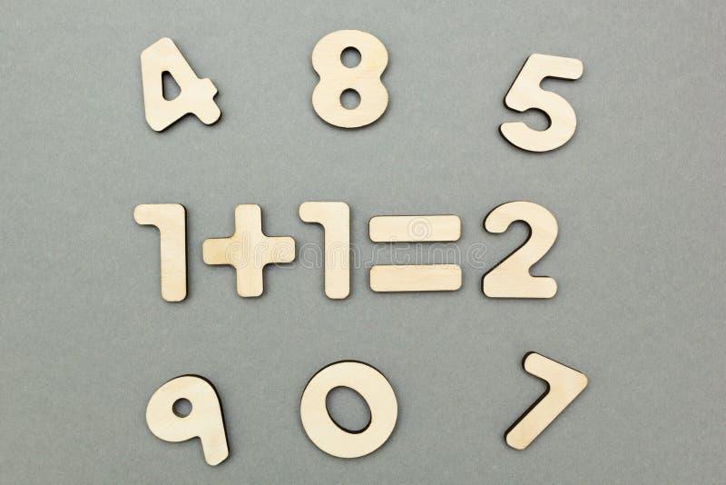Ένα παράδειγμα των ξύλινων αριθμών: το ένα συν έναν είναι δύο σε ένα γκρίζο υπόβαθρο υποβάθρου στοκ φωτογραφία με δικαίωμα ελεύθερης χρήσης