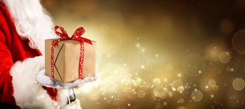 Ένα παρόν για τα Χριστούγεννα - εκλεκτής ποιότητας χρυσό υπόβαθρο με Άγιο Βασίλη στοκ εικόνα