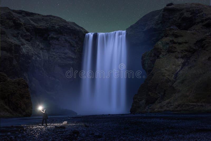 Ένα πεζοπορώ που στέκεται κάτω από τον καταρράκτη Skogafoss τη νύχτα στοκ εικόνα