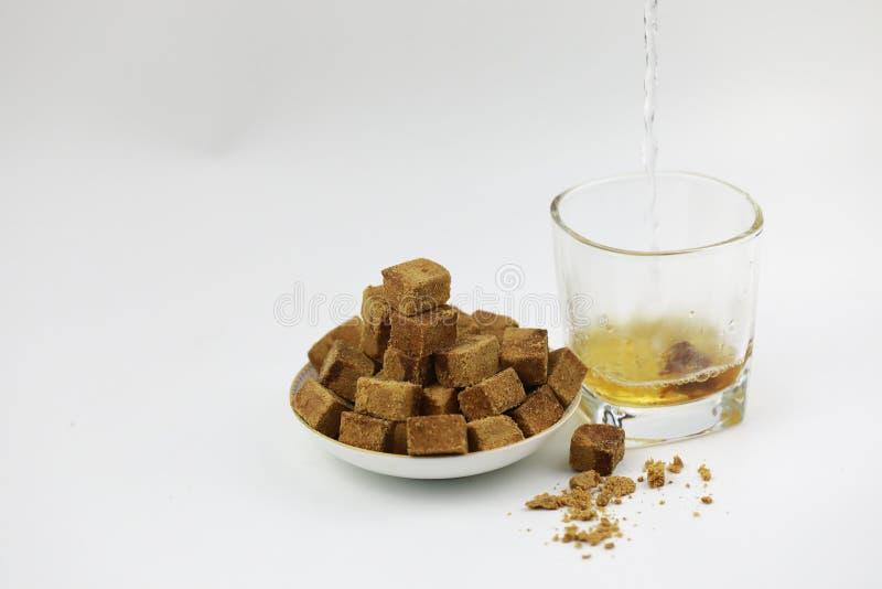 Ένα πιάτο της καφετιάς ζάχαρης κυβίζει τη ζάχαρη βράχου, καφετιά ζάχαρη σε ένα διαφανές ποτήρι, ένα κομμάτι της καφετιάς ζάχαρης  στοκ φωτογραφίες