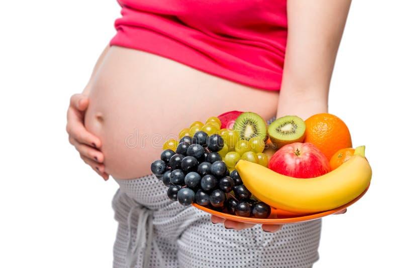 Ένα πιάτο των φρούτων στο υπόβαθρο της κοιλιάς ενός έγκυου wo στοκ εικόνα με δικαίωμα ελεύθερης χρήσης