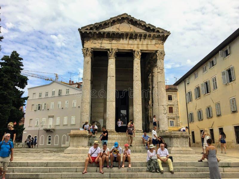 Ένα πλήθος των τουριστών που κάθονται μπροστά από, που παίρνουν τις εικόνες, και που θαυμάζουν τον καλά συντηρημένο ναό του Augus στοκ εικόνα