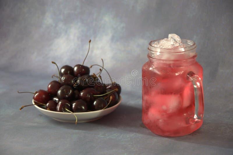 Ένα πλήρες πιατάκι των ώριμων φρέσκων κερασιών και μια κούπα γυαλιού με το χυμό κερασιών με τον πάγο E στοκ φωτογραφίες