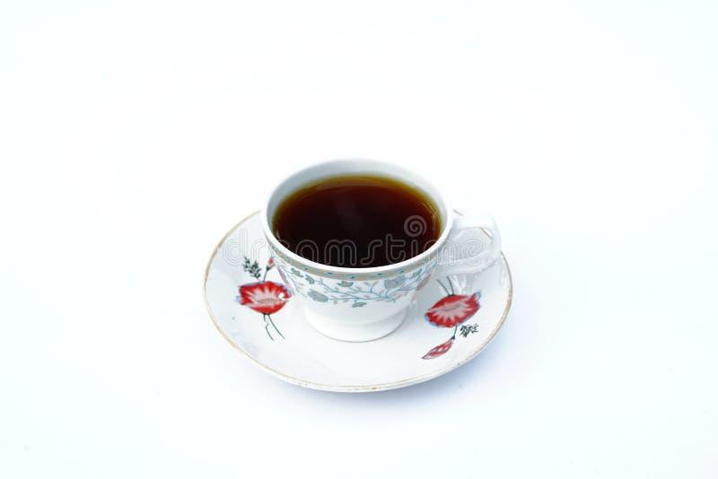 Ένα πλήρες φλιτζάνι του καφέ σε ένα πιάτο με το άσπρο υπόβαθρο στοκ φωτογραφίες