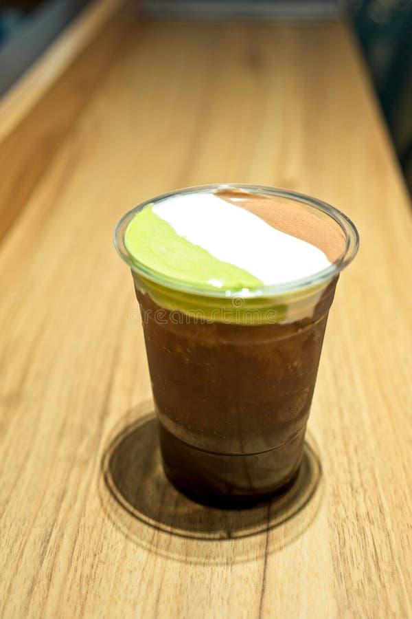Ένα πλαστικό ποτήρι του παγωμένου τσαγιού με το στρώμα του αφρού τυριών κρέμας, των καθιερωνόντων τη μόδα τροφίμων και των ποτών, στοκ εικόνες με δικαίωμα ελεύθερης χρήσης