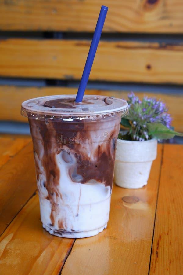 Ένα πλαστικό φλυτζάνι της σκοτεινών σοκολάτας και του γάλακτος με τον πάγο στοκ φωτογραφίες