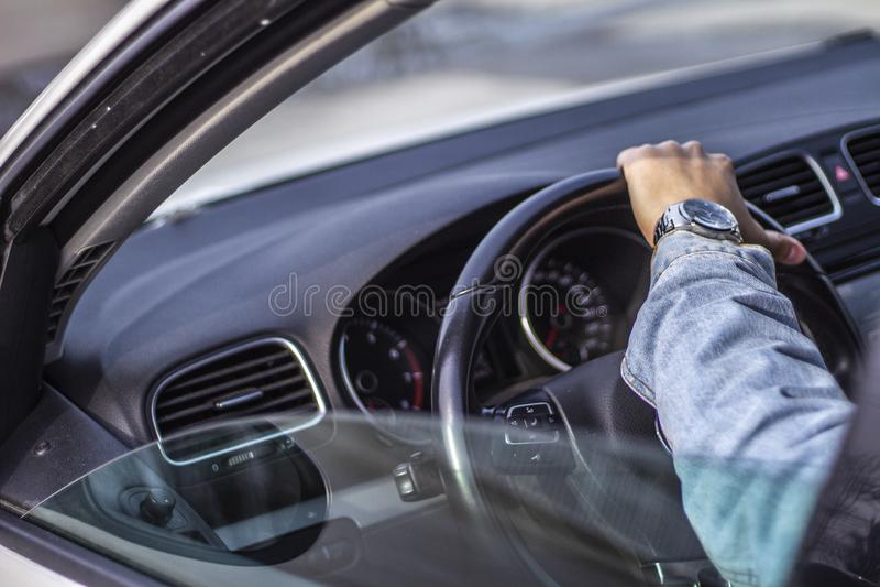 Ένα πλεόνασμα - ώμος που πυροβολείται ενός νεαρού άνδρα που κρατά το τιμόνι αυτοκινήτων στοκ εικόνες