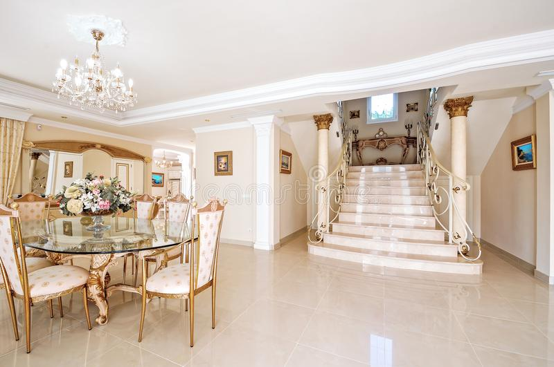 Ένα πολυτελές εσωτερικό με μια να δειπνήσει περιοχή και ένα μαρμάρινο πάτωμα και sta στοκ φωτογραφίες
