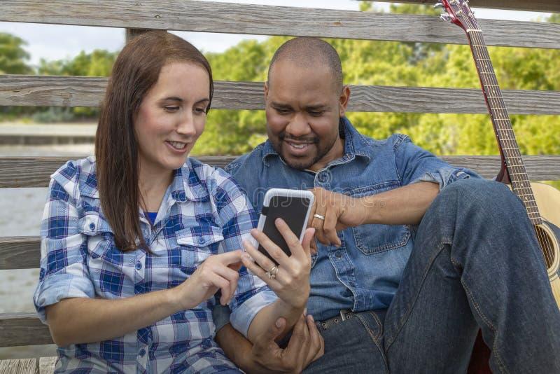 Ένα πολυφυλετικό ζεύγος κάθεται σε μια γέφυρα με ένα smartphone στοκ φωτογραφία