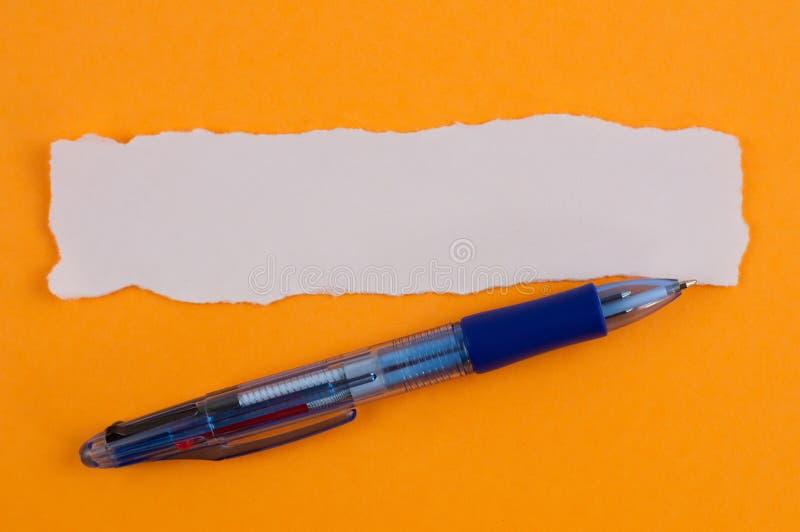Ένα πολυ μπλε διαφανές ballpoint χρώματος και άσπρο κενό σχισμένο ορθογώνιο έγγραφο για το υπόβαθρο του πορτοκαλιού στοκ εικόνες